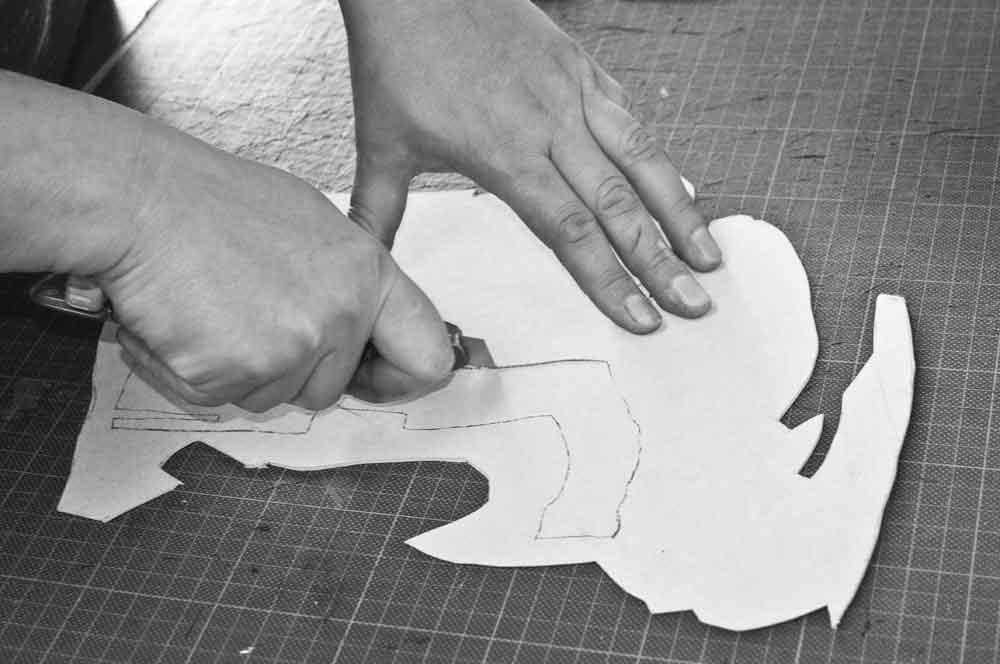 Hände schneiden eine Schablone aus