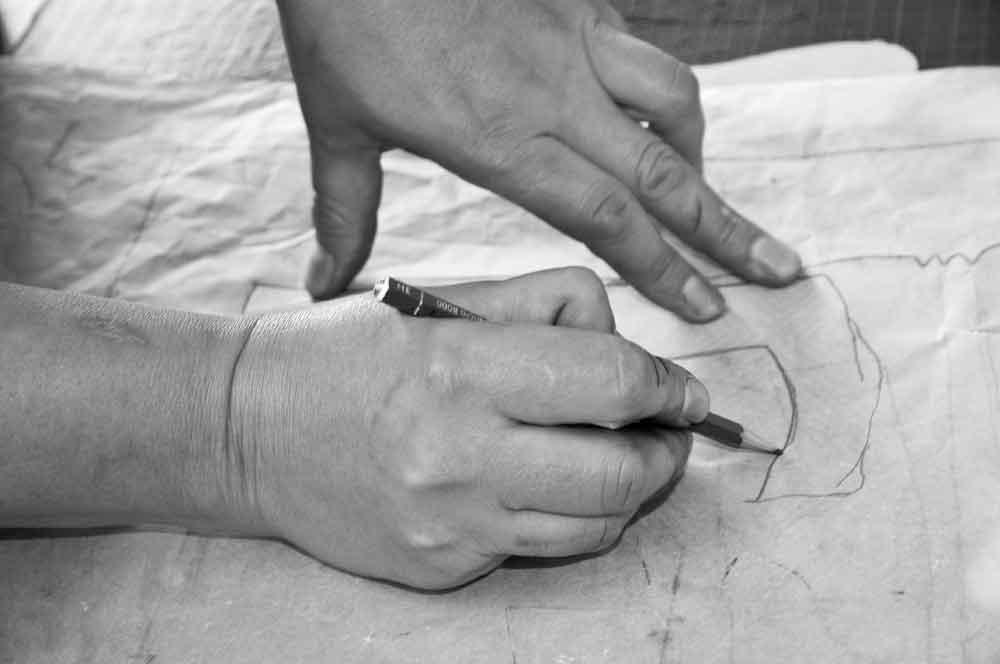 Hände zeichnen auf Pergamentpapier